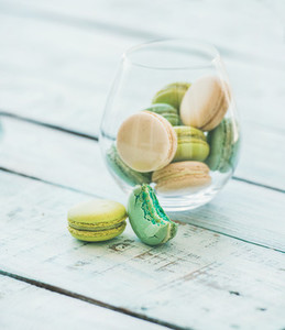 Colorful pastel French macaron biscuits in glass  wooden table background
