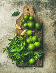 Flatlay of fresh limes and mint on rustic wooden board