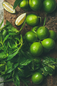 Flatlay of fresh limes and mint on wooden board background