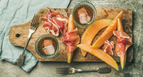 Flatlay of rose wine  prosciutto ham  melon  top view