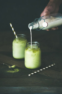 Refreshing iced coconut matcha latte drink in glass jars