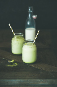 Refreshing iced coconut matcha latte drink in jars copy space