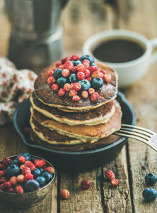 Breakfast with pancakes with forest berries and honey wooden background