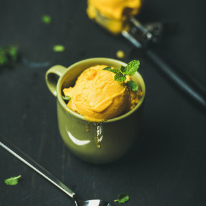 Mango sorbet ice cream scoops with fresh mint leaves