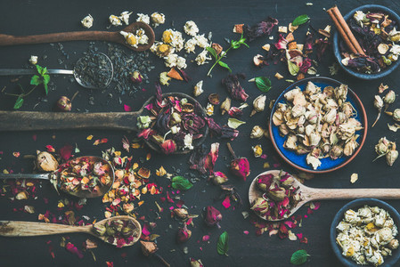 Wooden spoons with dry herbs  flower buds and tea leaves