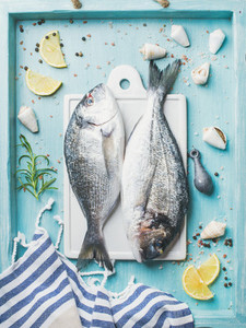 Fresh Sea bream raw uncooked fish with seasoning and lemon