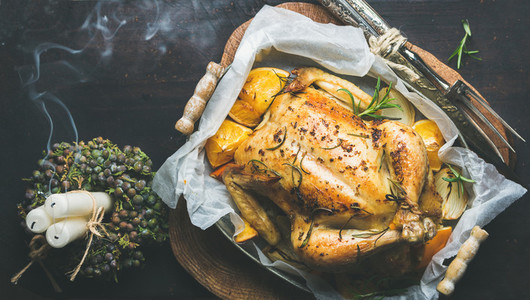 Christmas dinner with roasted chicken  rosemary and candle smoke