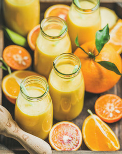 Healthy yellow smoothie in bottles with fresh fruits