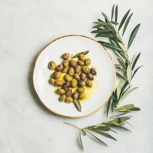 Pickled green Mediterranean olives in virgin olive oil  square crop