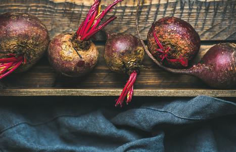 Raw organic purple beetroots in wooden box