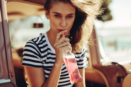 Woman drinking beverage on road trip