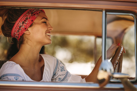 Beautiful woman driving a car and smiling