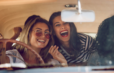 Friends going on vacation in a car and having fun