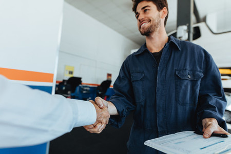 Auto mechanic shaking hands with satisfied customer