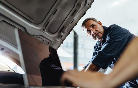 Mechanics working on a broken car in garage
