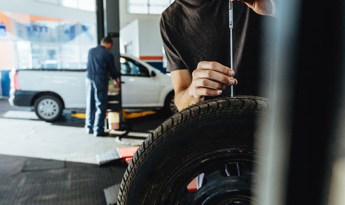 Mechanic checking car tire tread depth