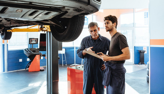 Auto mechanics making a list of repairs on car in service statio