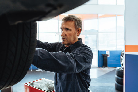 Mechanic changing wheel of a car in service station
