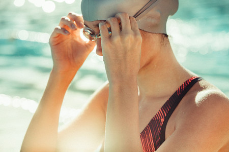 Professional female swimmer adjusting her goggles