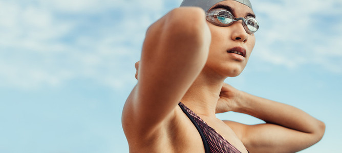 Female swimmer in swim cap and googles