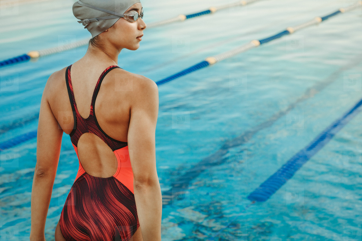 837551b4557 Photos - Professional female swimmer standing by the pool - YouWorkForThem