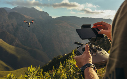 Nature photographer flying a drone in mountains