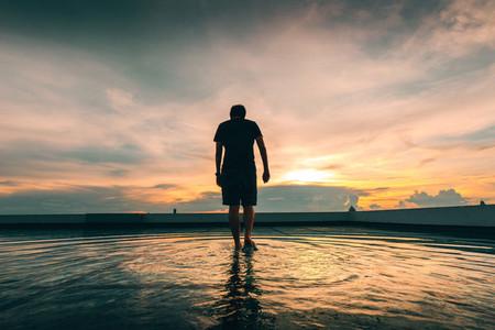 Man walking in water on rooftop