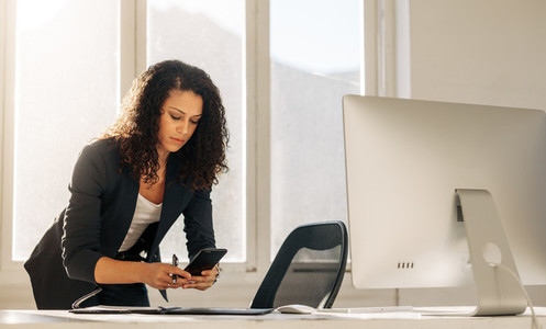 Woman entrepreneur using cell phone standing at her desk