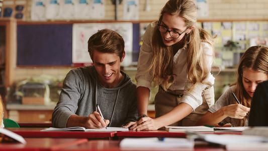 Teacher helping student during her class