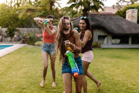 Female friends doing water gun battle