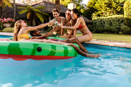 Multiracial group partying at private villa poolside