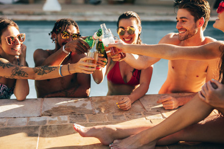 Group of friends toasting beer in a pool party