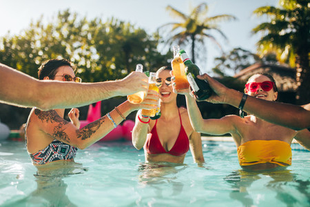 Group of friends toasting beers in swimming pool party