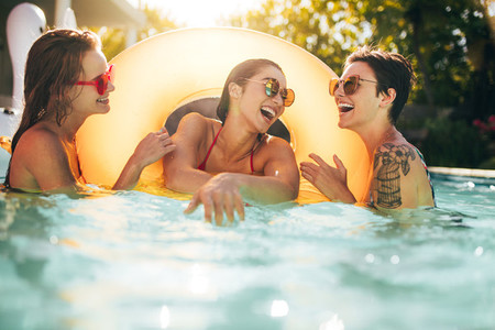 Friends laughing and enjoying in swimming pool