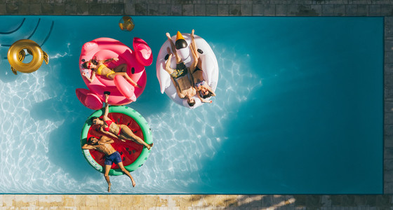 Friends relaxing on inflatable mattresses in pool