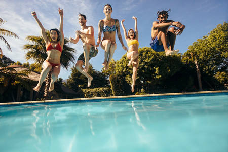 Friends jumping into a swimming pool and having fun