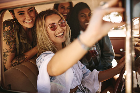 Woman driving a car and making selfie with friends