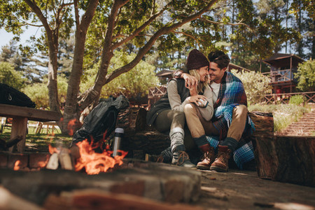 Couple in love sitting near a bonfire