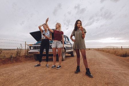 Woman with broken down car in middle of road trip