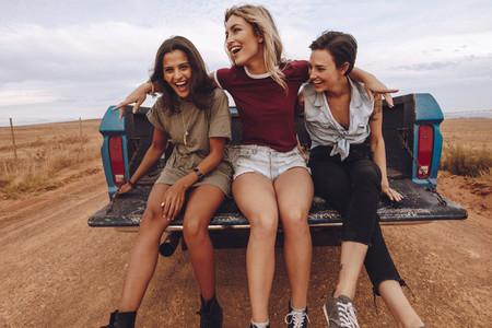Women traveling in a open back pickup truck