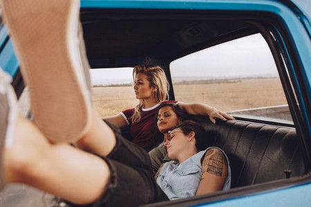 Woman driving car with friends resting
