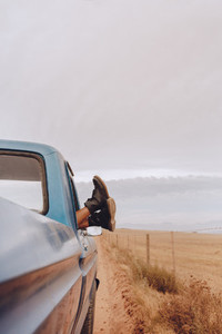 Woman relaxing in a car on road trip