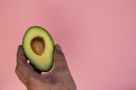 Hand holding avocado half on pink background minimal food