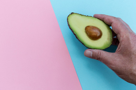 Hand holding avocado on pink background healthy food