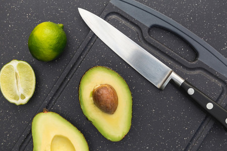 Avocado lime on chopping board with knife