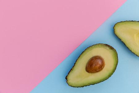 Avocado half on pink background minimal food