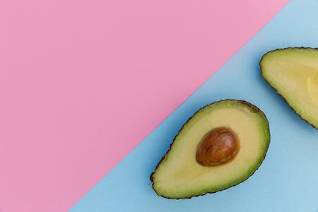 Avocado half on pink background minimal food