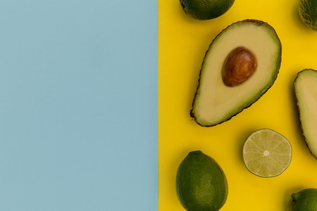 Avocado half on yellow background minimal food