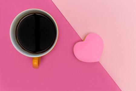 Coffee cup and love heart on pink background