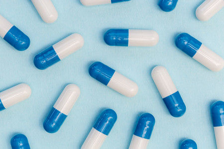 Drugs pills capsules on blue background abstract concept